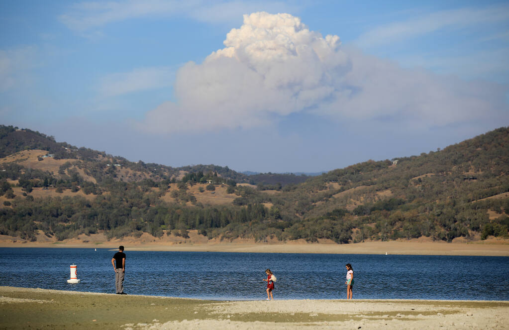 Vince Sims of Willits takes a walk with his daughters Stella, 7, Izabella, 11, on the drought baked shoreline on Lake Mendocino's south end, Monday, Aug. 21, 2020.  In the background is the August Complex fire.  (Kent Porter / The Press Democrat)
