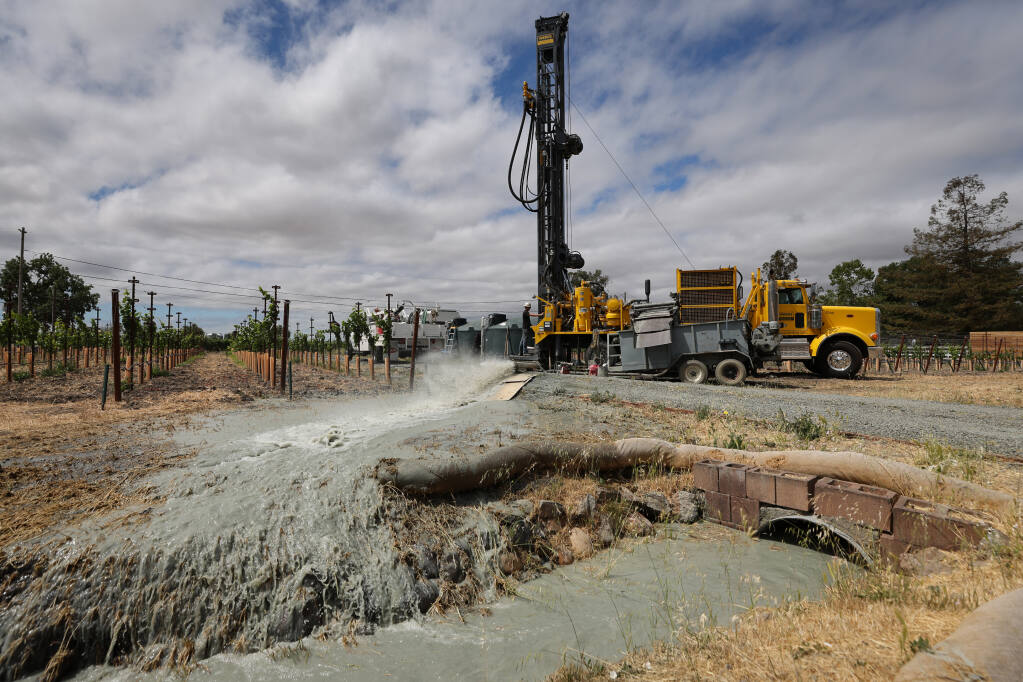 A crew from Weeks Drilling & Pump Co. test a new well, pumping into a self-contained ditch at a vineyard property near Sonoma on Tuesday, June 22, 2021.  (Christopher Chung / The Press Democrat)