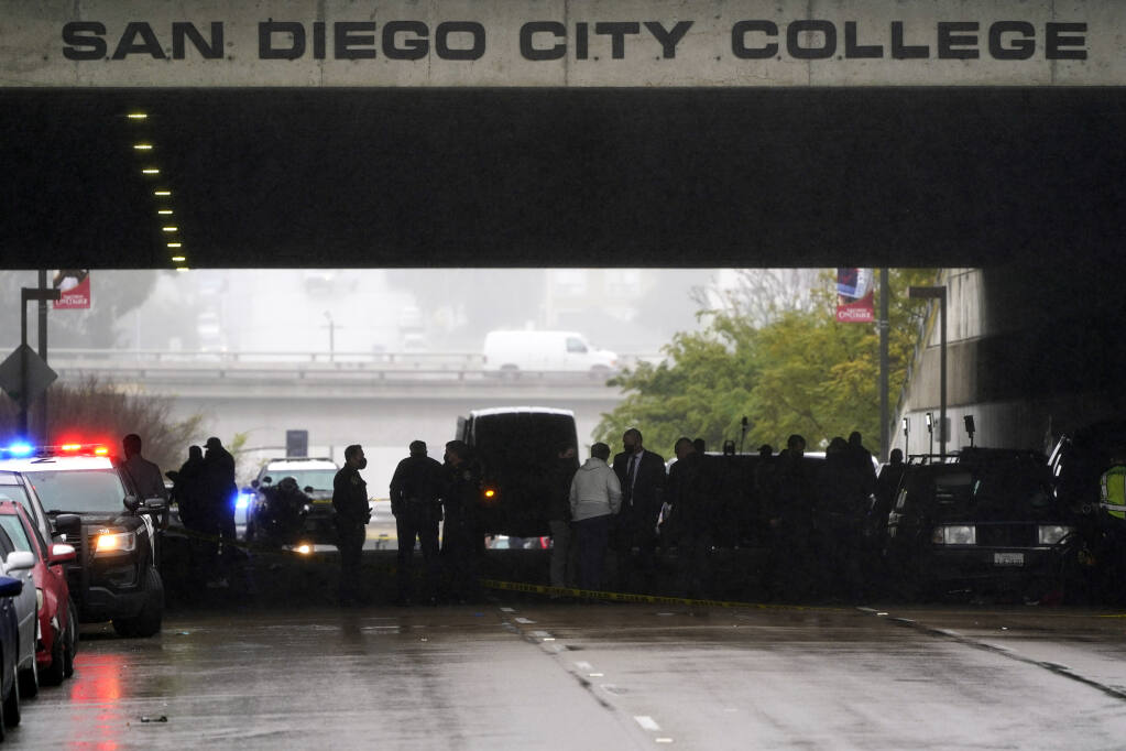 Emergency crews work at the scene of a deadly accident Monday, March 15, 2021, in San Diego. A driver plowed through a crowd on a sidewalk in downtown San Diego on Monday morning, killing three people and injuring six others, including two who are hospitalized in critical condition, police said. (AP Photo/Gregory Bull)