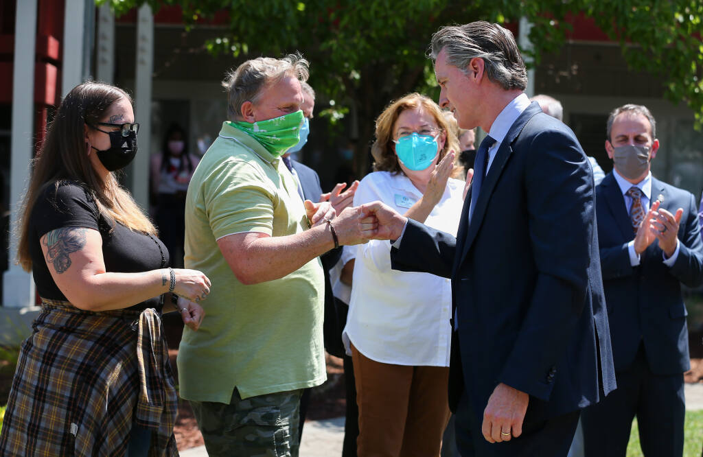 California Governor Gavin Newsom, right, fist bumps with  Elderberry Commons residents Douglas Stenberg and Claire Fulkerth after his press conference in Sebastopol on Monday, July 19, 2021.  (Christopher Chung/ The Press Democrat)