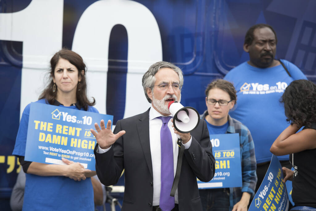 """San Francisco Supervisors Aaron Peskin (speaking) and Hillary Ronen, left, address supporters and the media as The Yes on 10 """"Rent Is Too Damn High"""" statewide bus tour arrives at City Hall ahead of the San Francisco Board of Supervisors endorsement of Proposition 10 on Tuesday, Oct. 2, 2018 in San Francisco. (Peter Barreras/AP Images for AIDS Healthcare Foundation)"""