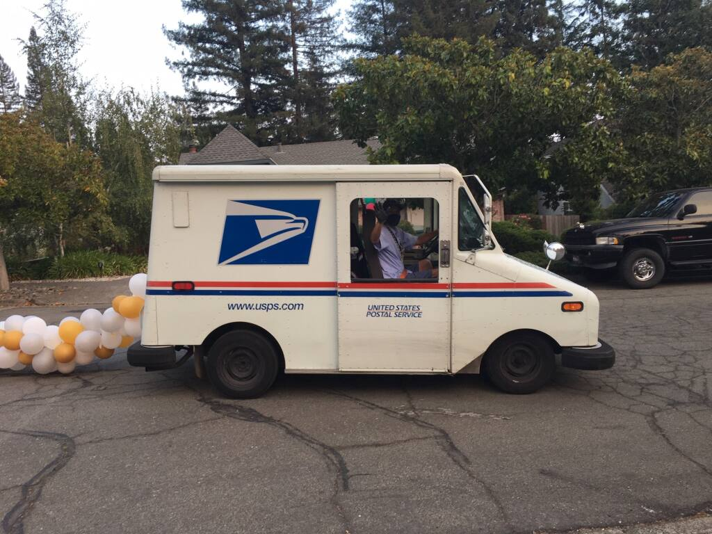 On his last day on the job, USPS carrier Tim Vega waves from the delivery van to which patrons tied a tail of balloons. (Beth Pitchford)