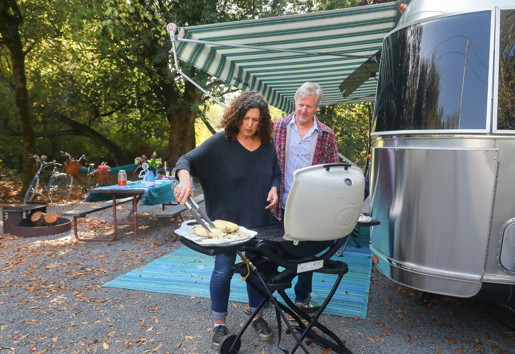 Claudia Sutton and John Stave prepare corn for Grilled Chipotle Corn Salad at the Duncans Mills Camping Club in Duncans Mills on Wednesday, Oct. 7, 2020.  (Christopher Chung / The Press Democrat)
