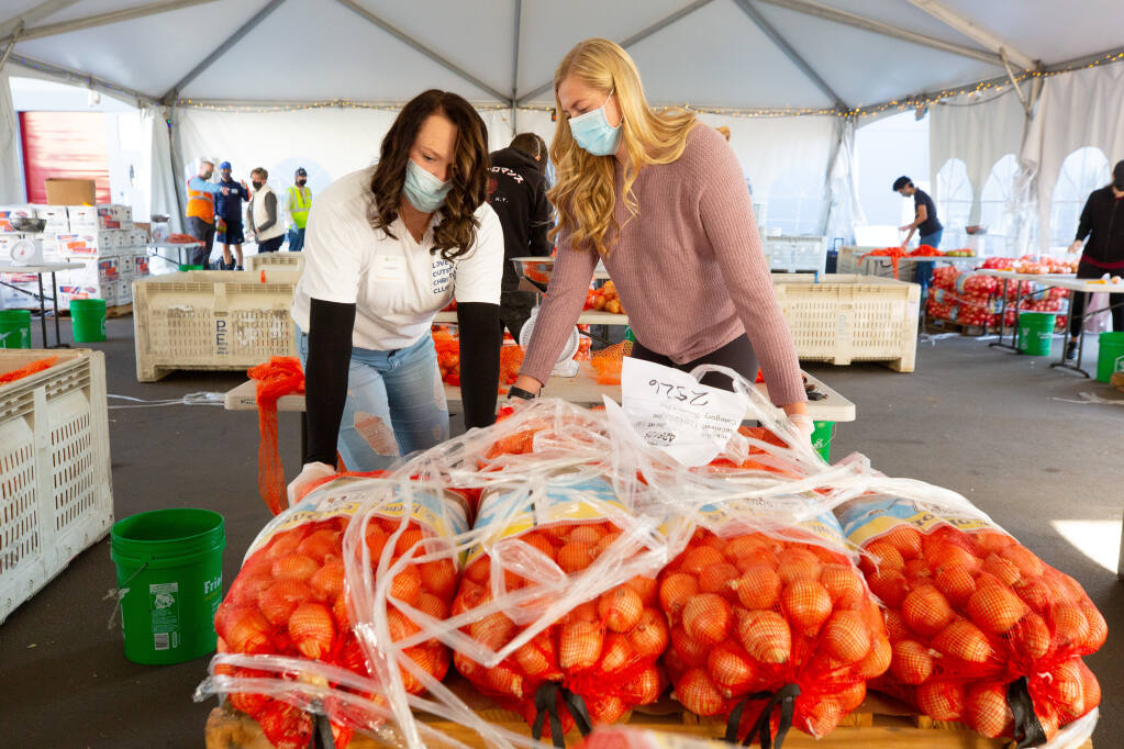 Windsor High School senior Hannah Dyer, left, and her sister Elena pull bags of onions off a pallet during a volunteer shift at the Redwood Empire Food Bank in Santa Rosa, California, on Friday, Dec. 4, 2020. (Alvin A.H. Jornada / The Press Democrat)