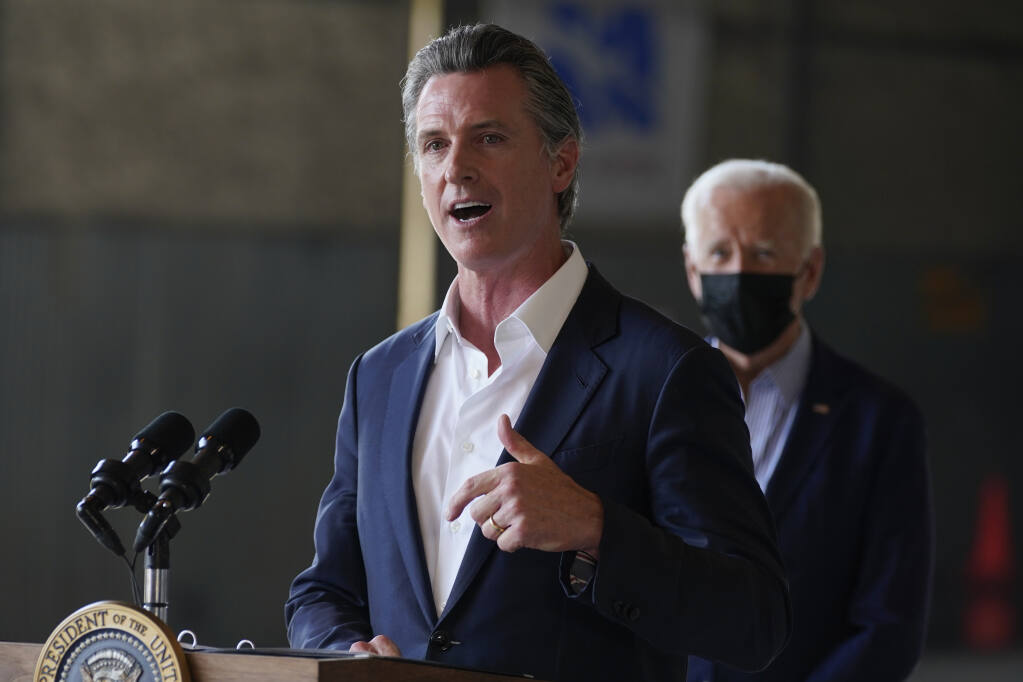 President Joe Biden listens as California Gov. Gavin Newsom speaks about recent wildfires, at Sacramento Mather Airport, Monday, Sept. 13, 2021, in Mather, Calif. (AP Photo/Evan Vucci)
