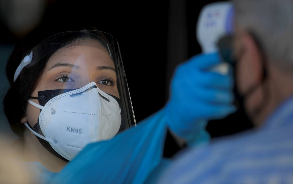 Andrea Guerrero takes the temperature of a man as he enters a  COVID-19 vaccination site in Windsor, Wednesday, Feb. 10, 2021.   (Kent Porter / The Press Democrat) 2021