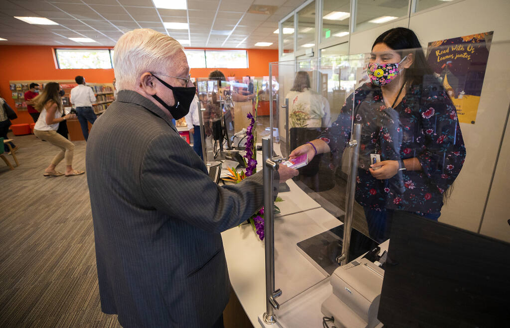Dave Cahill checks out the second book from librarian Guadlaupe Guzman at the new Roseland Regional Library  on Monday, September 13, 2021. (Photo by John Burgess/The Press Democrat)