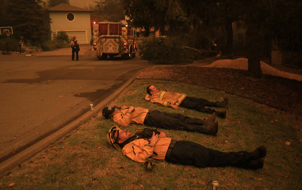 Healdsburg firefighters Mike Jacobs, Dean De La Montoya and Bennett Lida rest after saving structures overnight on Beaumont Way, Monday, Sept. 27, 2020 in Santa Rosa. Only one home was lost on the block as the Glass fire roared in to Rincon Valley overnight. (Kent Porter / The Press Democrat) 2020