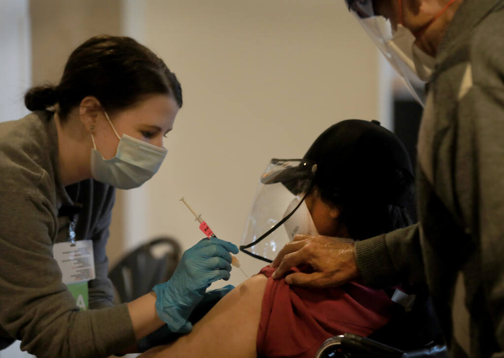 Registered nurse Morgan Longacre injects the Modena vaccine in to Meera Goyan of Santa Rosa during a Sutter Santa Rosa Regional Hospital COVID-19 vaccination clinic at the Luther Burbank Center in Santa Rosa, Tuesday, Feb. 9, 2021.Her husband Gaeshav, right, also received the vaccine.   (Kent Porter / The Press Democrat)