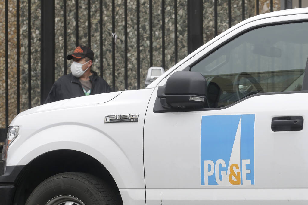 FILE - In this April 16, 2020, file photo, a man wearing a mask walks behind a Pacific Gas and Electric truck in San Francisco. (AP Photo/Jeff Chiu, File)