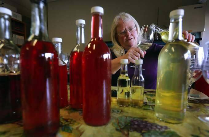 Carol Shelton tries samples of the 2014 Wild Thing Chardonnay, right, and the 2014 Wild Thing Dry Rose of Carignane at her Santa Rosa winery. Shelton was making the final tweaks to the blends before bottling next week. (Photo by John Burgess/The Press Democrat)