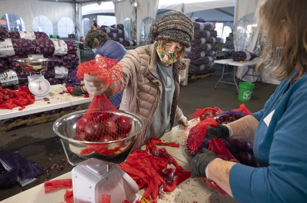 Volunteer Leah Harmon weighs a bag of onions at the Redwood Empire Food Bank in Santa Rosa on Thursday, February 4 2021. With demand for food continuing to soar amid the pandemic, the regional food bank is desperate for more volunteers. (Photo by John Burgess/The Press Democrat)