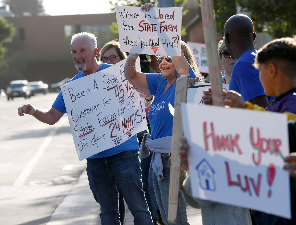 Fire survivors Jim and LuAnn Scally, residents of Coffey Park, encourage motorists to honk their support during Friday's rally for fire survivors who will be losing their insurance coverage at the second anniversary of the North Bay wildfires. (ALVIN JORNADA / The Press Democrat)