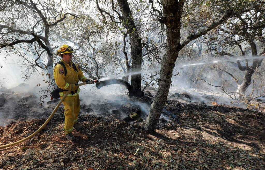 Firefighters protect structures off of 7th St. East in Sonoma on Saturday, October 14, 2017. Several homes were burned in the area overnight. (John Burgess/The Press Democrat)