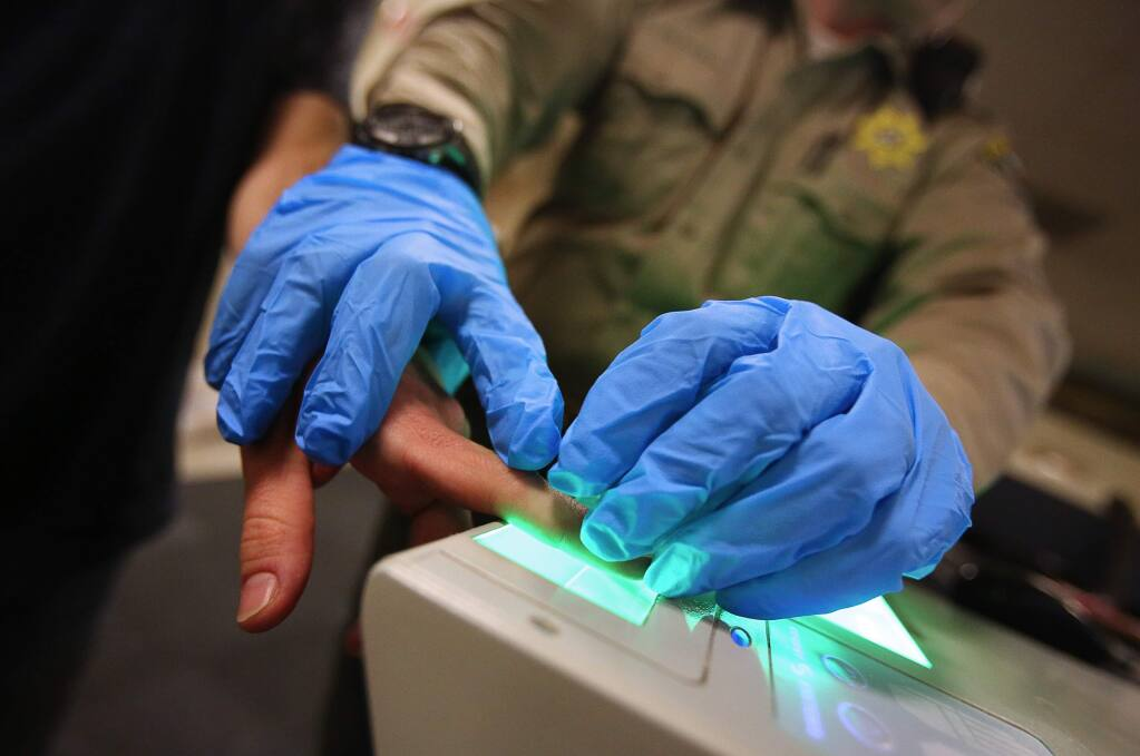 An individual is fingerprinted by a Sonoma County Sheriff's deputy while being processed at the Main Adult Detention Facility, in Santa Rosa, on Thursday, February 9, 2017. (Christopher Chung/ The Press Democrat)