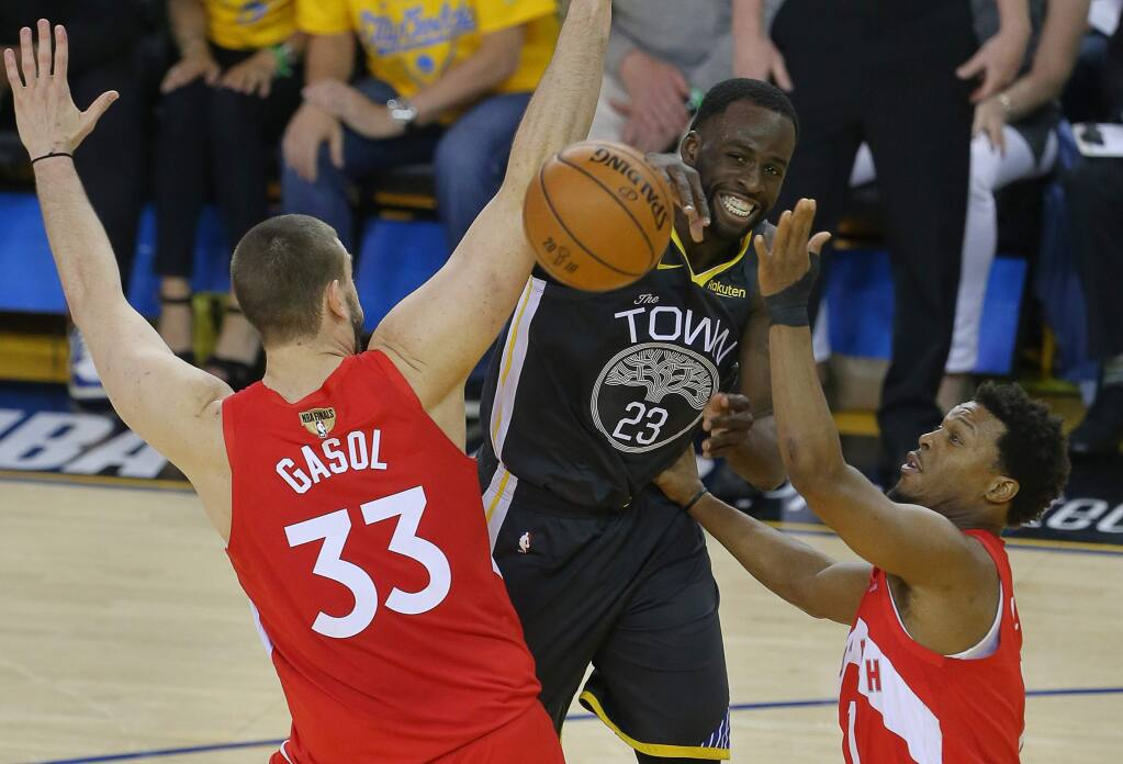 Golden State Warriors forward Draymond Green passes the ball between Toronto Raptors center Marc Gasol and guard Kyle Lowryduring game 4 of the NBA Finals in Oakland on Friday, June 7, 2019. (Christopher Chung/ The Press Democrat)