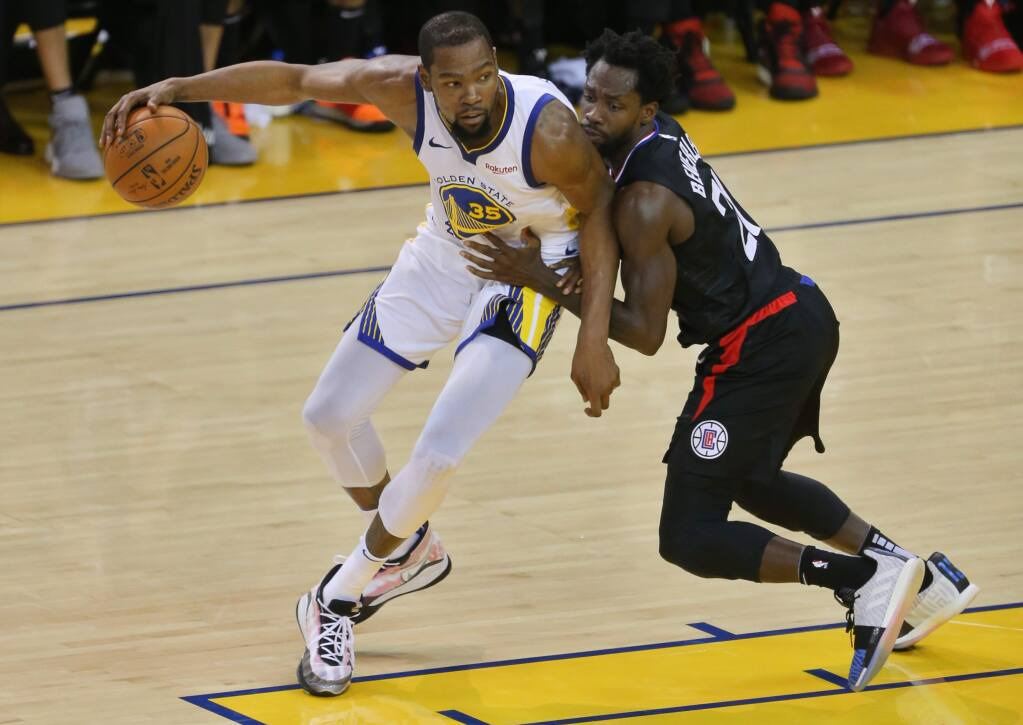 Golden State Warriors forward Kevin Durant backs down toward the basket against Los Angeles Clippers guard Patrick Beverley during a playoff game in Oakland on Saturday, April 13, 2019. (Christopher Chung / The Press Democrat)