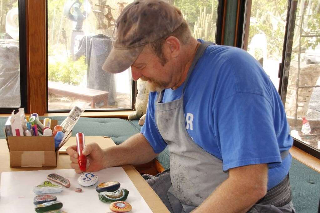 Sculptor T Barny paints a rock at his gallery and studio in the Alexander Valley in preparation for International Sculpture Day. Ann Carranza
