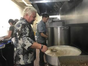 Guy Fieri cooks meals for first responders who have battled the Kincade fire with his son, Hunter, at the Sonoma County Fairgrounds in Santa Rosa on Thursday, Oct. 31, 2019. (Elissa Chudwin/ The Press Democrat)