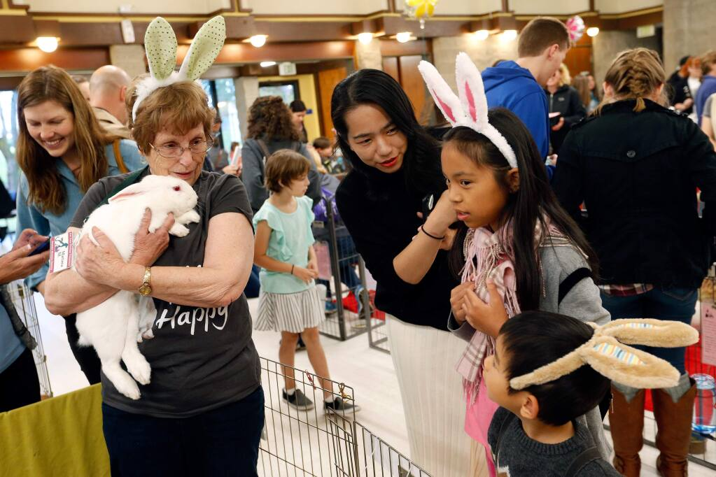 Sonoma Humane Society volunteer Mariana Moats, left, holds a bunny while talking with Tracy Ding of Santa Rosa and her children Rachel, 11, and Jasper, 4, during Bunfest at Burton Avenue Recreation Center in Rohnert Park, California, on Saturday, April 8, 2017. (Alvin Jornada / The Press Democrat)