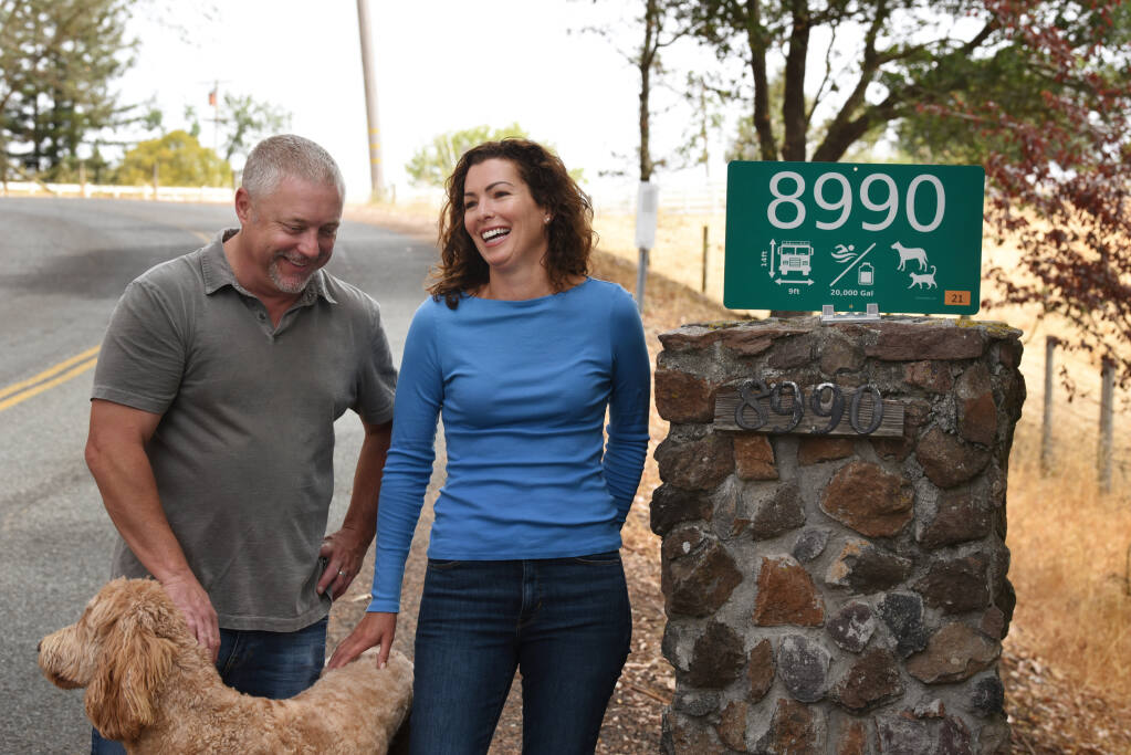 Brant Claussen, left, and Joanie Benedetti Claussen with their fire safe sign at the entrance to their home in Cotati, Calif. on Saturday, July 3, 2021. The couple have created a sign system to help first responders with critical property information during fires and other emergencies.(Photo: Erik Castro/for The Press Democrat)
