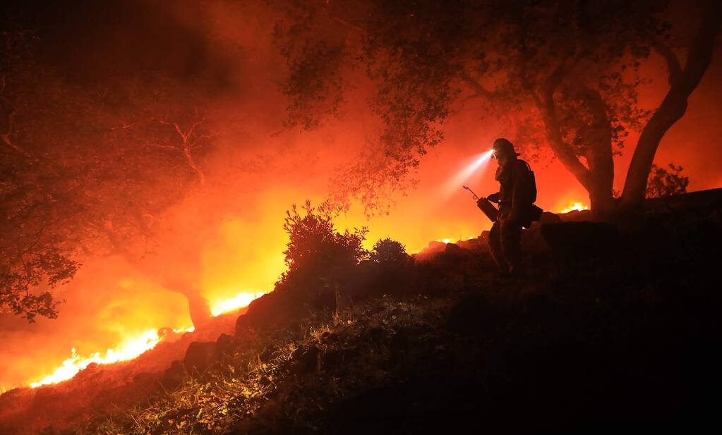 A San Diego Cal Fire firefighter monitors a flare up on a the head of the Nuns fire (the Southern LNU Complex), Wednesday Oct. 11, 2017 off of High Road above the Sonoma Valley. A wind shift caused flames to move quickly up hill and threaten homes in the area. (Kent Porter / Press Democrat) 2017