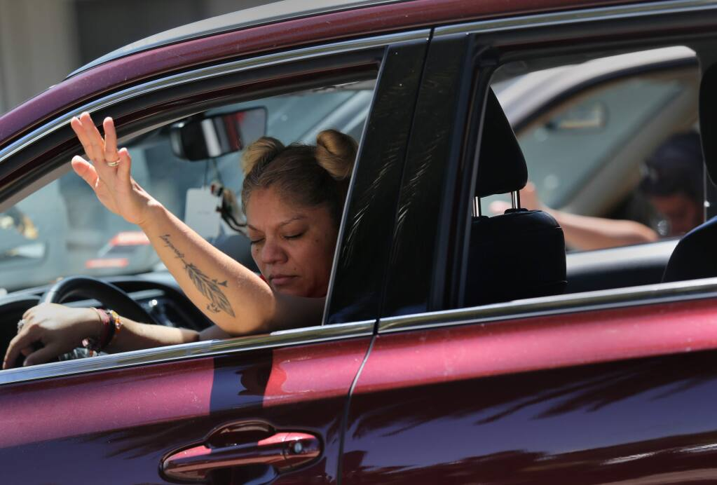 Leny Camara, left, and Kaye Martin, right, remain in their cars as they attend a Park-N-Praise service in Victory Outreach Santa Rosa church parking lot in Santa Rosa, Calif., on Sunday, May 24, 2020. (BETH SCHLANKER/ The Press Democrat)