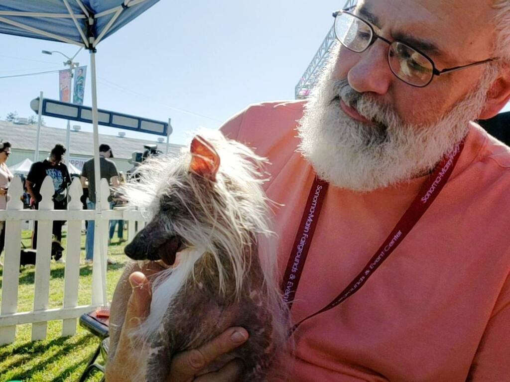 Kelly Wilson of Oregon holds his family dog Moogie before the start of the World's Ugliest Dog Contest at the Sonoma-Marin Fair in Petaluma, California on Friday, June 21, 2019. (Alvin Jornada/The Press Democrat)