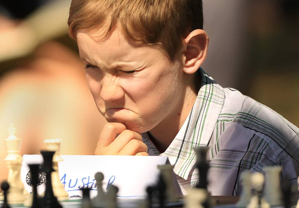 Austin Richter, 10, of Santa Rosa contemplates his next move against Los Angeles-based Armenian-born American chess grandmaster Varuzhan Akobian as he and others from Santa Rosa's Chess for Kids played Akobian at Paradise Ridge Winery in Santa Rosa on Monday, June 6, 2016. (KENT PORTER/ PD)