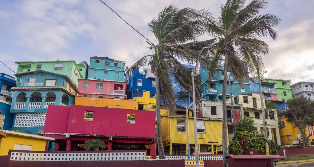 Buildings are painted in vibrant colors along a street in La Perla, a historic shanty town in Puerto Rico. (Saara Snow)