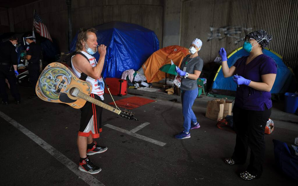 Billy Blankenship is coached by Sandra Castano, right, and Amy Bradbury from the Petaluma Health Center as Blankenship takes a swab test for the coronavirus at the Sixth Street homeless camp in Santa Rosa, Saturday, June 20, 2020. (Kent Porter / The Press Democrat) 2020