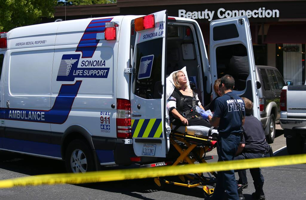 Emergency personnel place a woman injured in a Santa Rosa jewelry store robbery into an ambulance. (CHRISTOPHER CHUNG / The Press Democrat, 2014)
