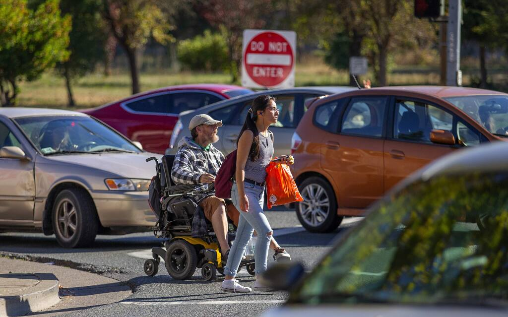A disabled man in a wheelchair and a pedestrian try to make their way across Stony Point Rd. at the Hwy 12 exit ramp on Tuesday afternoon. Jennell Marie Davies, 39, of Santa Rosa was struck and killed by a truck while walking in the same crosswalk last Tuesday, October 23, 2018. (photo by John Burgess/The Press Democrat)