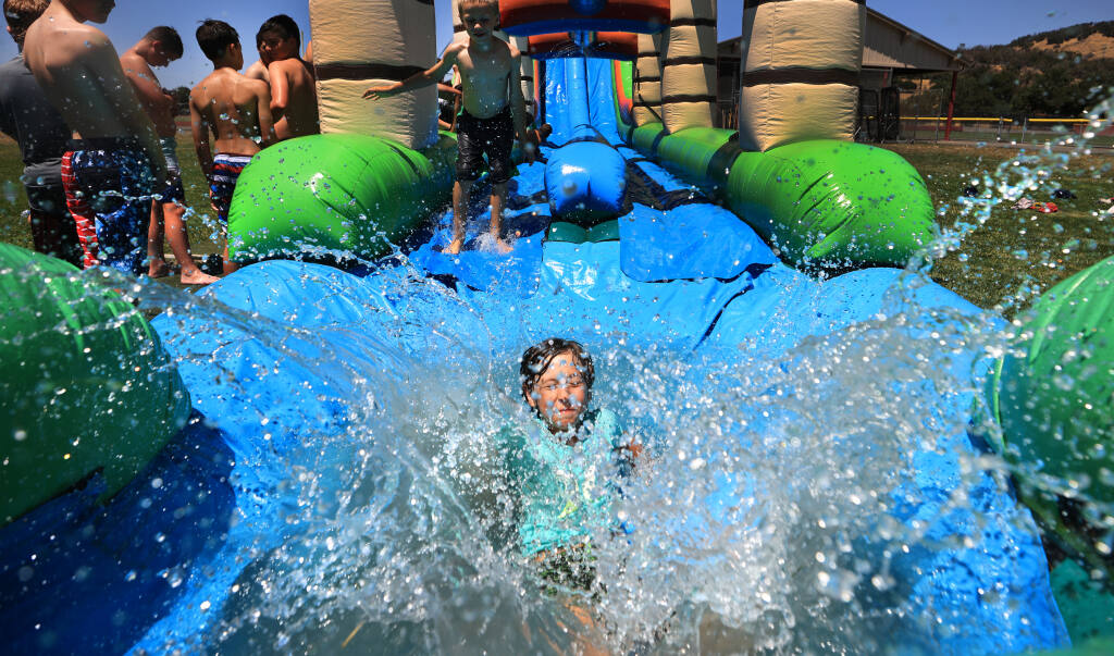 Nine year-old Roland Blum barrels into the end of  a slip-and-slide jump near the last day of a four-day baseball camp  for 6-13 year-olds, Thursday, June 17, 2021 at Cardinal Newman High School.  The jump was a last minute decision by the coaches due to the heat. (Kent Porter / The Press Democrat)