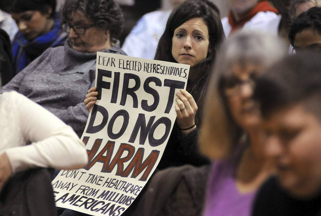 Amy Kuiken holds a sign during a town hall meeting regarding health care Tuesday in Scranton, Pa. Sen. Pat Toomey, R-Pa., was invited but didn't attend the meeting. (BUTCH COMEGYS / Scranton Times-Tribune)