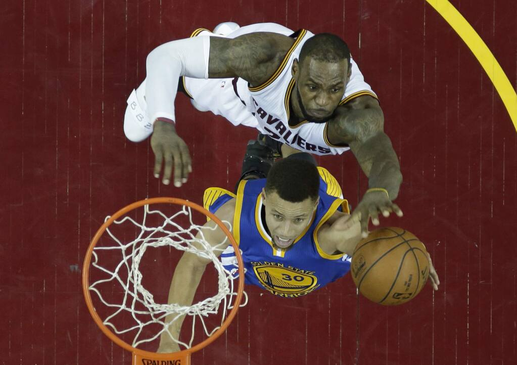 Golden State Warriors' Stephen Curry, bottom, drives to the basket against Cleveland Cavaliers' LeBron James in the second half in Game 6 of the NBA Finals, Thursday, June 16, 2016, in Cleveland. The Cavaliers won 115-101. (AP Photo/Ron Schwane)