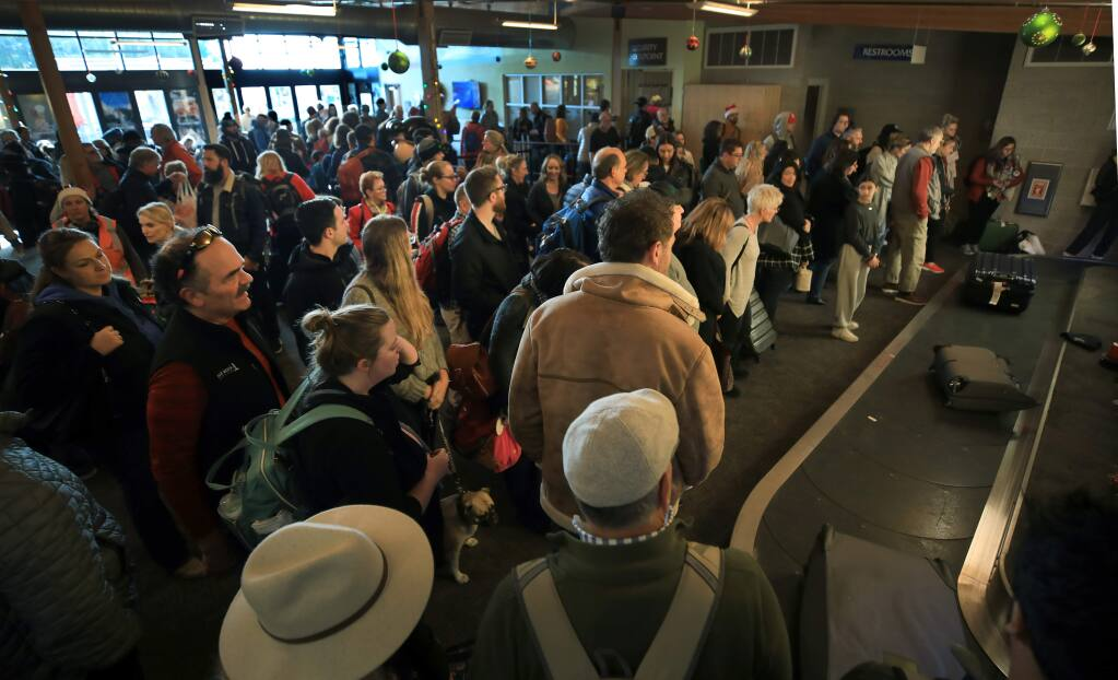 Passengers wait for their bags at the crowded terminal at the Charles M. Schulz Sonoma County Airport on Tuesday, Dec. 24, 2019. (Kent Porter / The Press Democrat) 2019