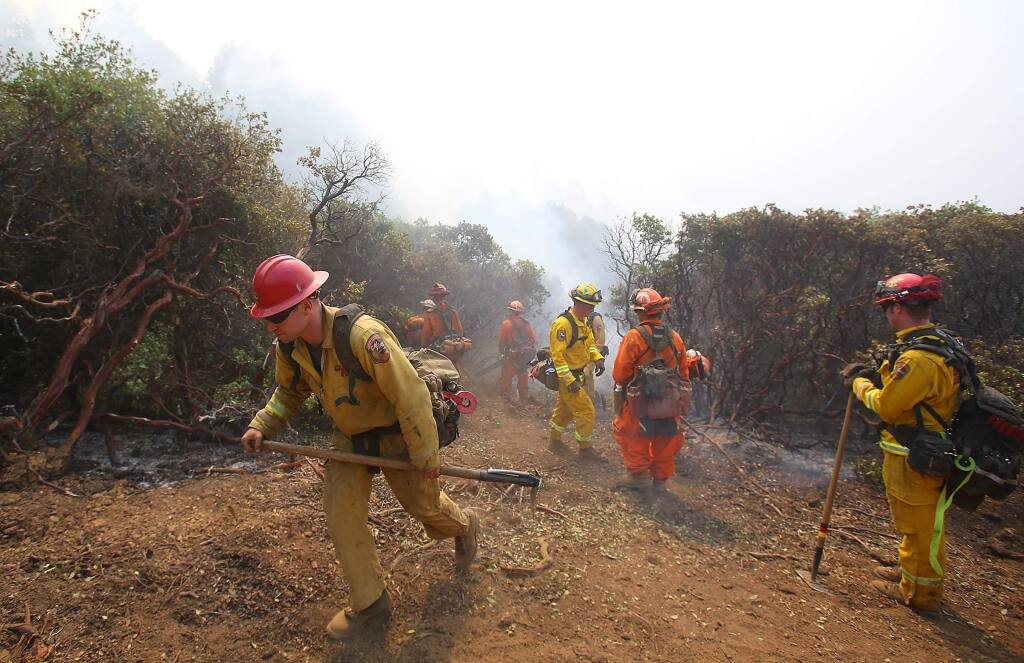 The Toulomne-Calaveras Cal Fire Unit and an inmate crew prepare to set a blackline, from the holding line to the oncoming fire, in order to create a buffer at the northeast corner of the Lodge Complex Fire, north of Laytonville on Monday, Aug. 11, 2014. (Christopher Chung / The Press Democrat)