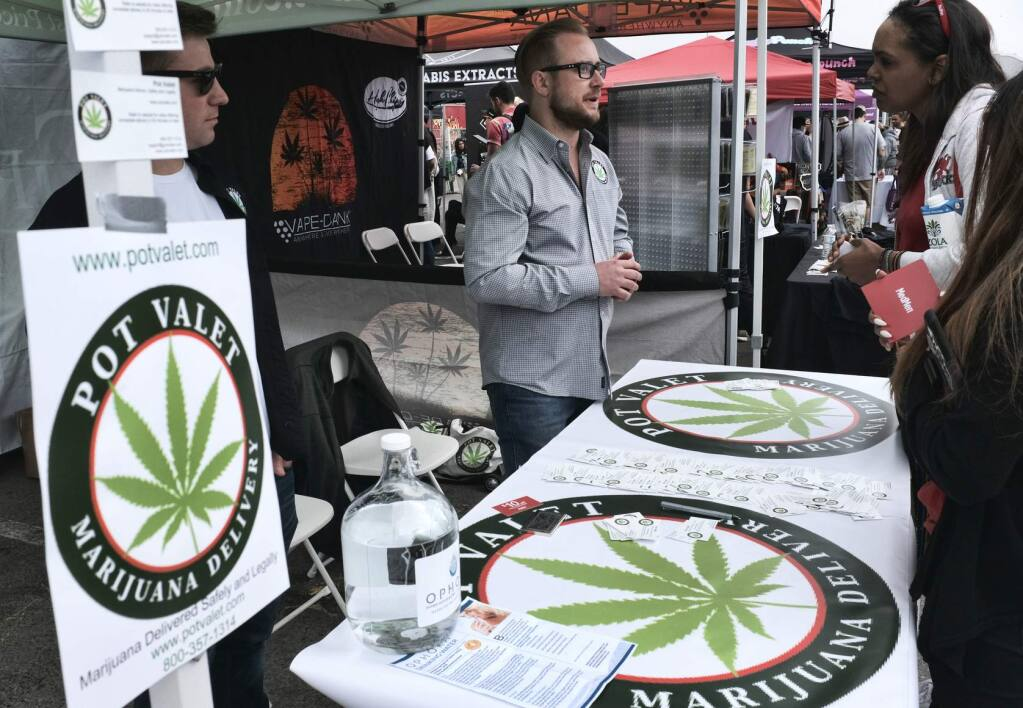 FILE - This March 31, 2018 photo shows a booth advertising a delivery service for cannabis at the Four Twenty Games in Santa Monica, Calif. Three California agencies released proposed regulations Friday, Dec. 7, 2018, for the state's marijuana industry including deliveries that will become permanent next month after state lawyers finish their review of them. Law enforcement groups and cities with marijuana bans unsuccessfully fought against it. (AP Photo/Richard Vogel, File)