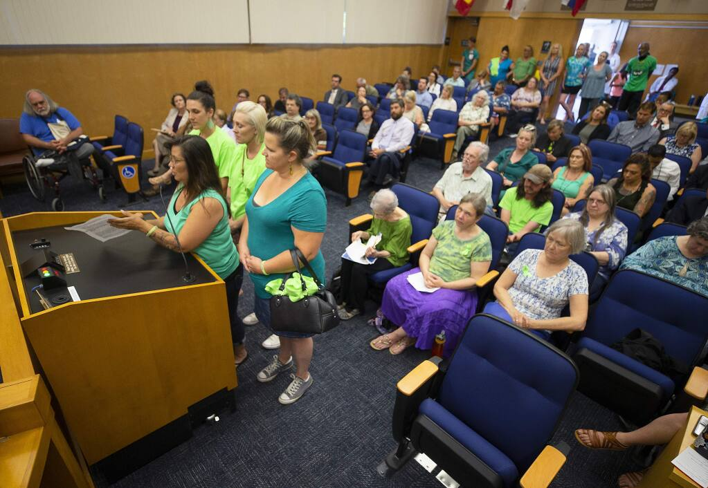 Tanya Sarcos, left at podium, an employee with the Santa Rosa Treatment Program, brought her Rollin Rosie's Car Club friends to support her and funding for mental health and addiction education during public discussion of the budget at the Sonoma County Board of Supervisors on Tuesday. (photo by John Burgess/The Press Democrat)
