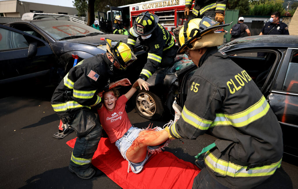 Gracie McNulty, 19, attempts to stifle a laugh as Northern Sonoma County firefighters, Colby Jenkins,  Andre Gluch and David Alvarez participate in an extrication drill during the Northern Sonoma County Fire and Earthquake Expo, Saturday, August 7, 2021 in Cloverdale.  (Kent Porter / The Press Democrat) 2021