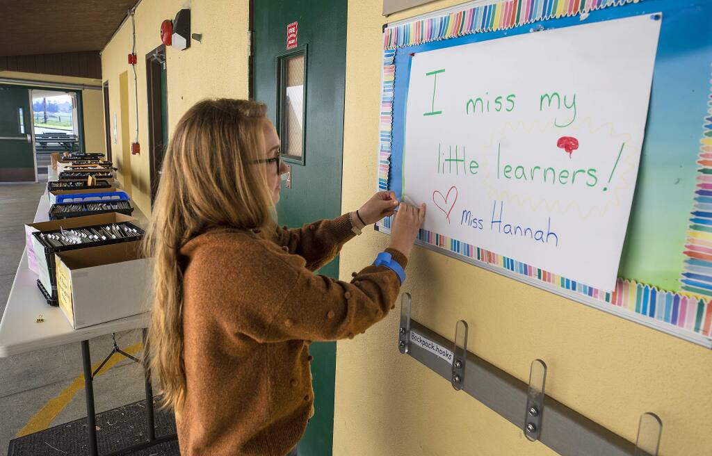 Hannah Long, a transitional kindergarten teacher at Two Rock Elementary, hangs a sign for her students to read when they pick up their homework packets at the rural west county school. (photo by John Burgess/The Press Democrat)