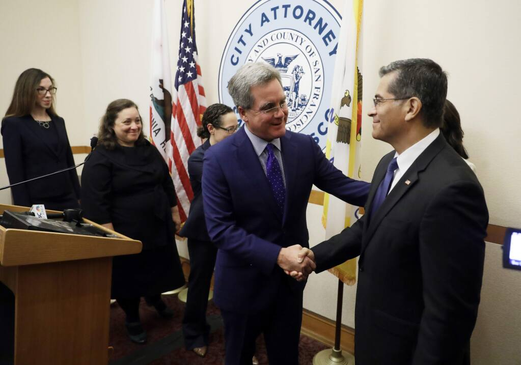 California Attorney General Xavier Becerra, right, shakes hands with San Francisco City Attorney Dennis Herrera during a press conference at San Francisco City Hall Monday, Aug. 14, 2017, in San Francisco. The state of California and city of San Francisco are suing the U.S. Department of Justice over President Donald Trump's sanctuary city restrictions on public safety grants. (AP Photo/Marcio Jose Sanchez)