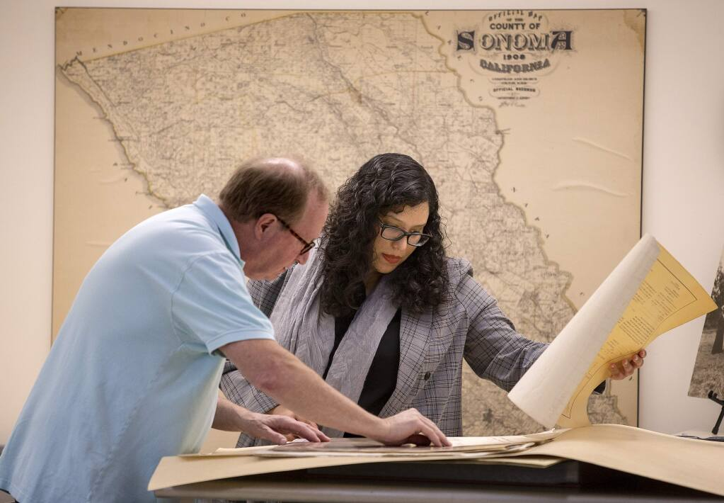 Sonoma County History and Genealogy librarian Zayda Delgado searches through old maps with David Proctor, who was looking for the location of his house when it was moved to build Hwy 101 60 years ago. (photo by John Burgess/The Press Democrat)