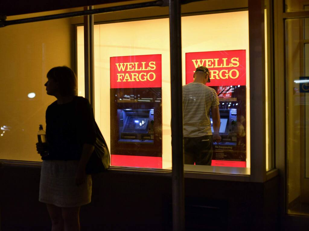 FILE - In this Sept. 21, 2016, file photo, a customer uses a Wells Fargo bank ATM in New York. (AP Photo/Patrick Sison, File)