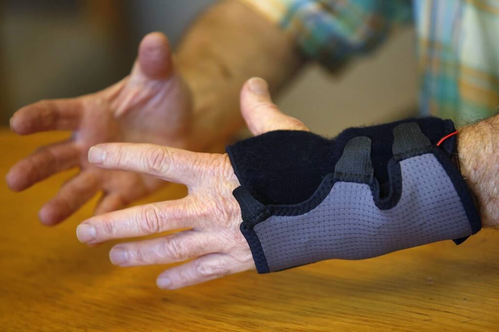 Neurology researcher Dr. Allan Bernstein tries on a digital glove that can help neurologists track the progression of Parkinson's disease and hopefully treat it more effectively in Santa Rosa on Tuesday, September 16, 2014. The glove was developed by a group of interdisciplinary undergraduate research students from Sonoma State University. (Conner Jay/The Press Democrat)