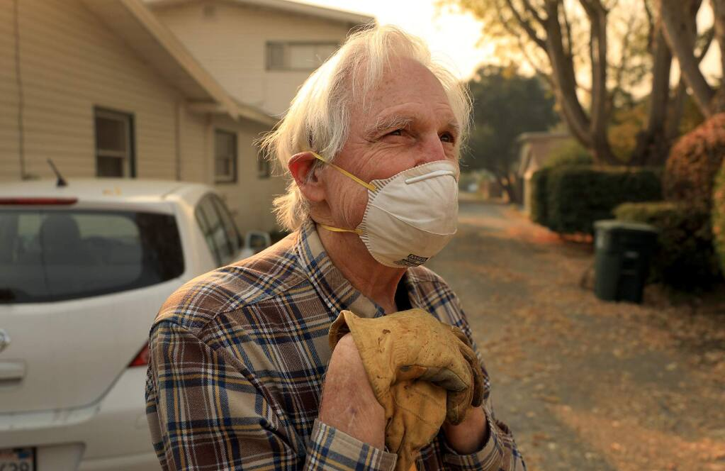 """Steve Smith takes a rest from raking leaves near his home in Santa Rosa, as he wears a mask because of the Camp fire in Butte County, Thursday, Nov. 8, 2018. Sonoma County health officials said Friday morning local air quality reached """"very unhealthy"""" levels. (Kent Porter / The Press Democrat) 2018"""