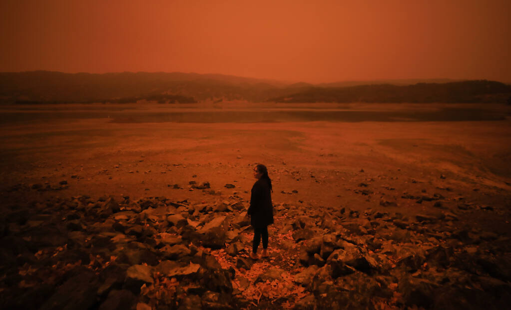 Drought-plagued Lake Mendocino, coupled with dense smoke from the August Complex and other Northern California wildfires, gives reason for Fernanda Chavez of Ukiah to pause at the Mars-like surroundings, Wednesday, Sept. 9, 2020  (Kent Porter / The Press Democrat) 2020