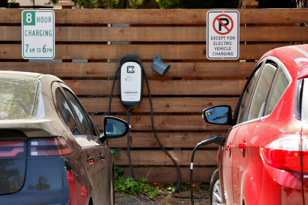 A pair of electric cars are plugged in at the bank of employee vehicle charging stations at the offices of Jackson Family Enterprises in Santa Rosa, California, on Wednesday, May 31, 2017. (Alvin Jornada / The Press Democrat)