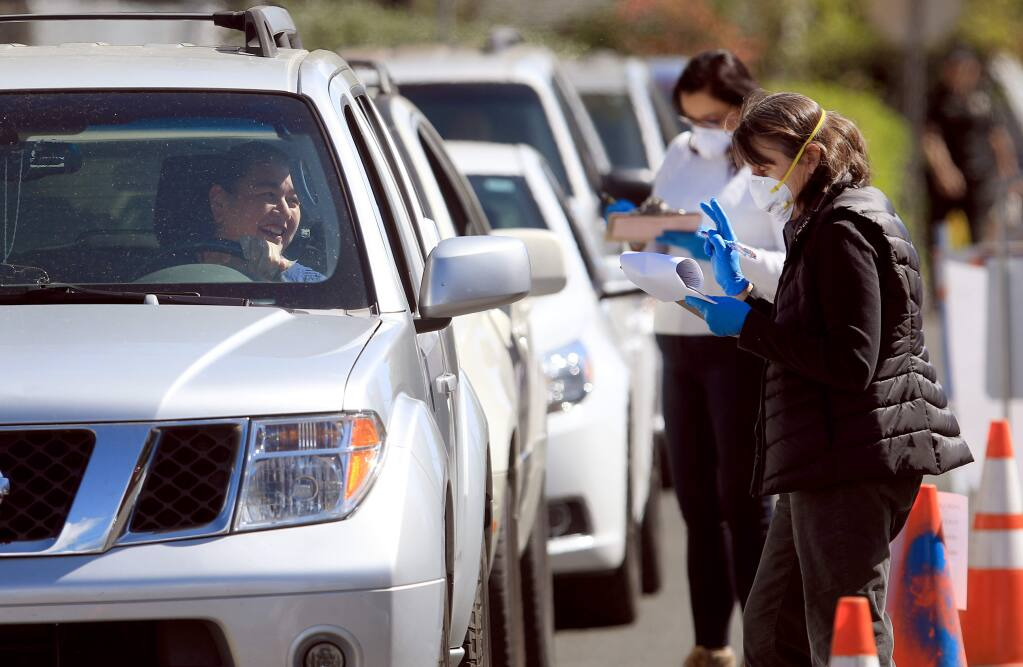 Volunteers with Groceries to Go hand out food to Healdsburg residents during a mobile food giveaway at Healdsburg Elementary School, Thursday, March 26, 2020. (Kent Porter / The Press Democrat) 2020